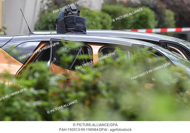 13 May 2019, Brandenburg, Forst: An explosives expert in protective equipment stands between two open cars in a parking lot
