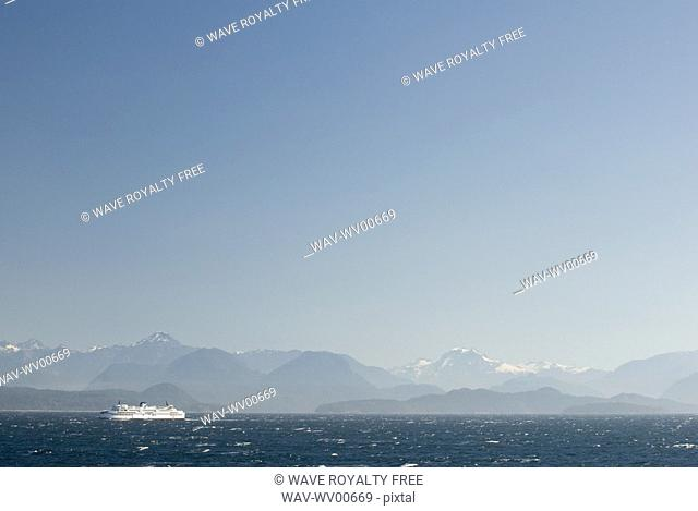 Ferry boat makes a crossing in rough seas with mountains in the background, BC Ferries, Nanaimo, BC, Canada