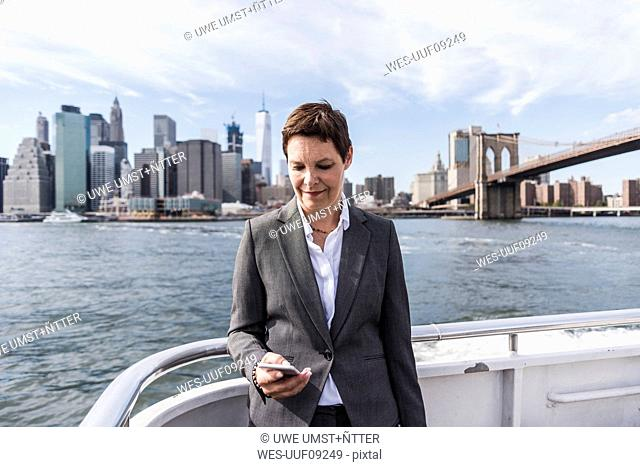 USA, Brooklyn, portrait of businesswoman standing on boat looking at cell phone