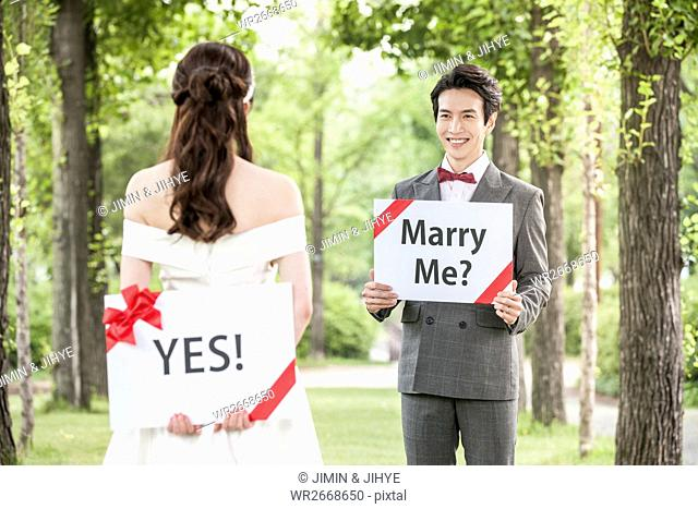 Young romantic wedding couple with English messages outdoors