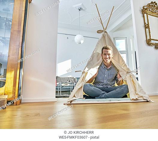 Smiling man sitting on floor in a teepee