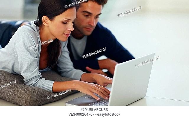 Happy young couple smiling while using a laptop and browsing online