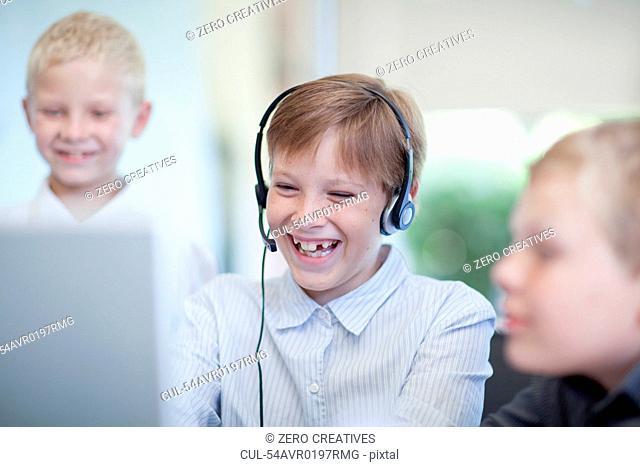 Boys playing businessmen at desk