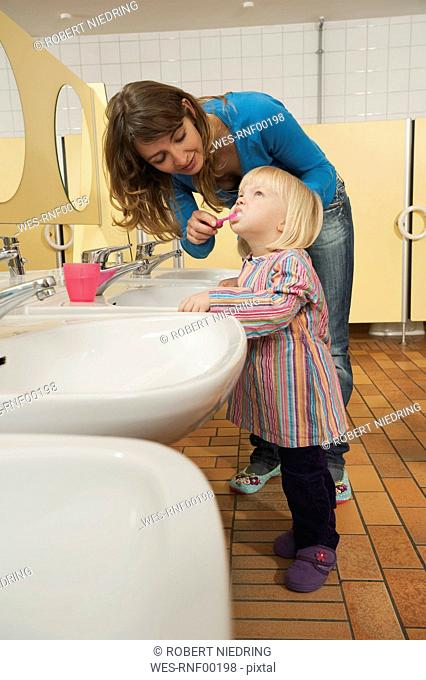 Germany, Female nursery teacher and girl 3-4 in lavatory, female teacher helping girl to brush her teeth, side view, portrait