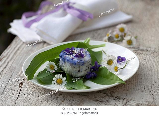 Goat's cheese with violets and daisies on ramsons wild garlic