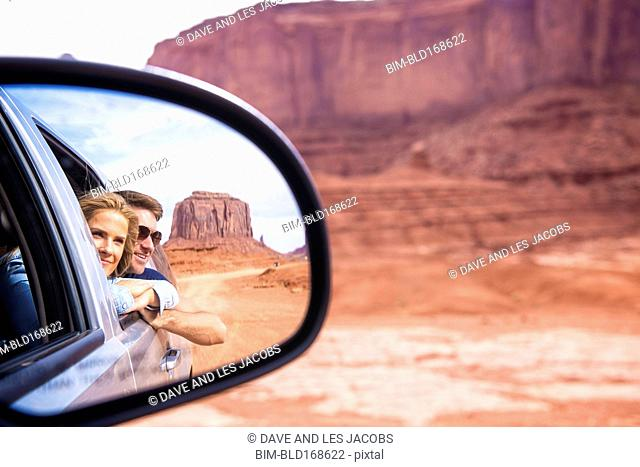 Reflection of Caucasian couple in side-view mirror, Monument Valley, Utah, United States