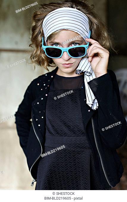 Serious girl peering over sunglasses