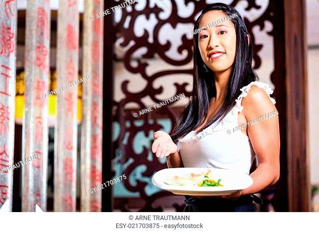 Kellnerin in asiatischem Restaurant mit Sushi