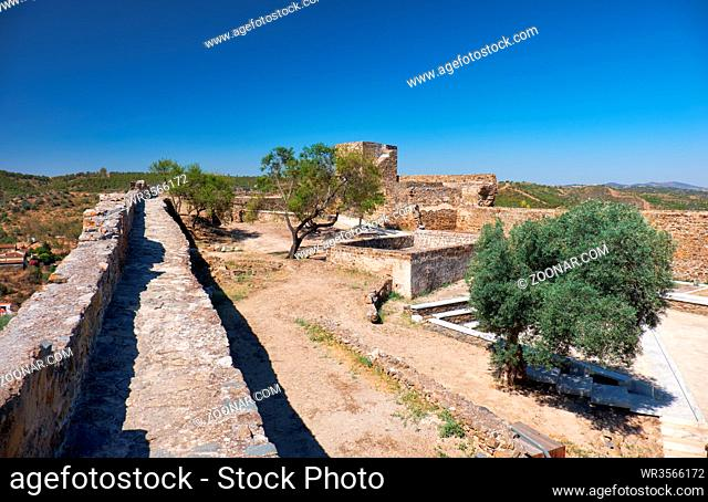 The view of the fortress wall and inner courtyard of the Mertola Castle with the Carouche Tower on the background. Mertola. Portugal