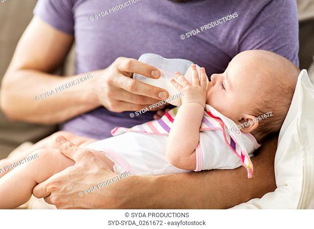 close up of father feeding baby from bottle
