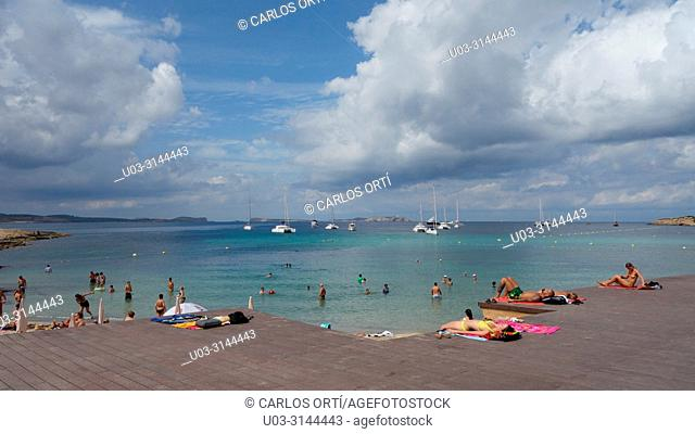 Tourists sun bathing in a beach near the balearic town of Sant Antoni de Portmany, in the north of the island of Ibiza, Spain, Europe