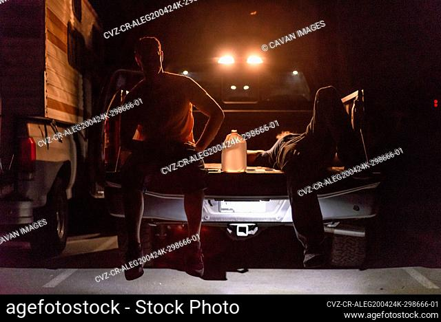 two men resting sitting back of truck backlit in the night water jug