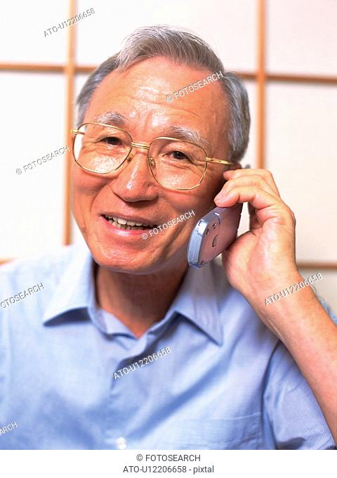 Senior adult man talking on a mobile phone, Front View
