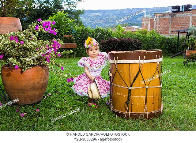 little girl in traditional dance dress with flower bandana next to a drum