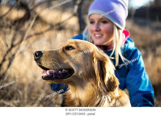 A golden retriever with it's female owner; Anchorage, Alaska, United States of America