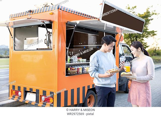 Young smiling couple at food truck