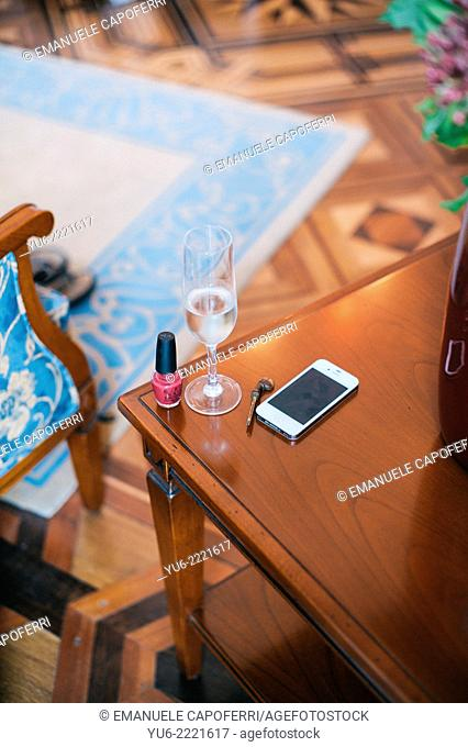 Coffee table with glass of wine, polish, Phones