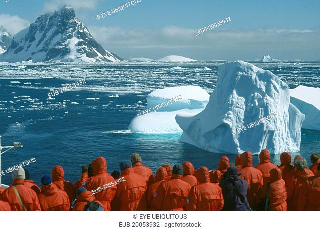 Tourist group looking at iceberg from cruise ship near the Lemaire Channel