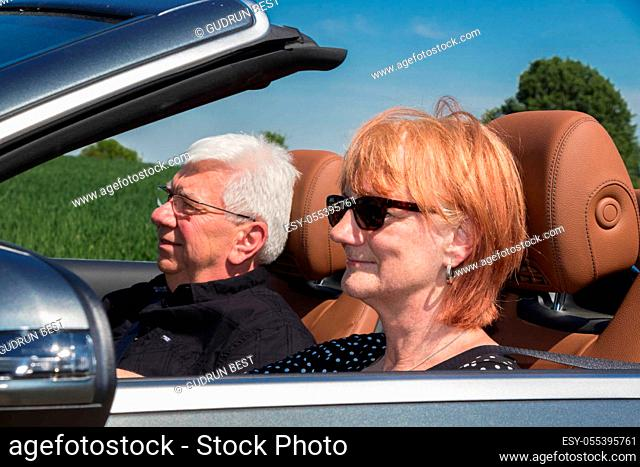 Senior woman with partner driving a car
