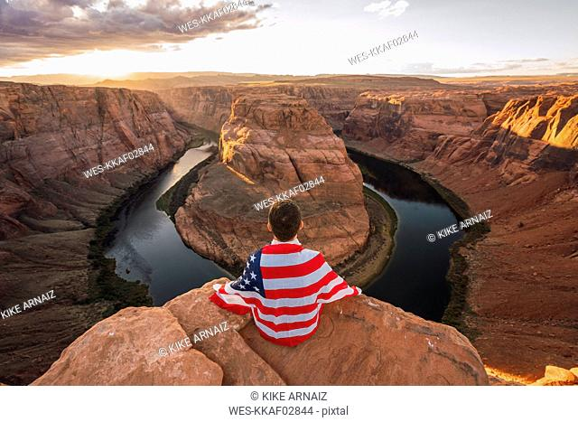 USA, Arizona, Colorado River, Horseshoe Bend, young man sitting on viewpoint with American flag