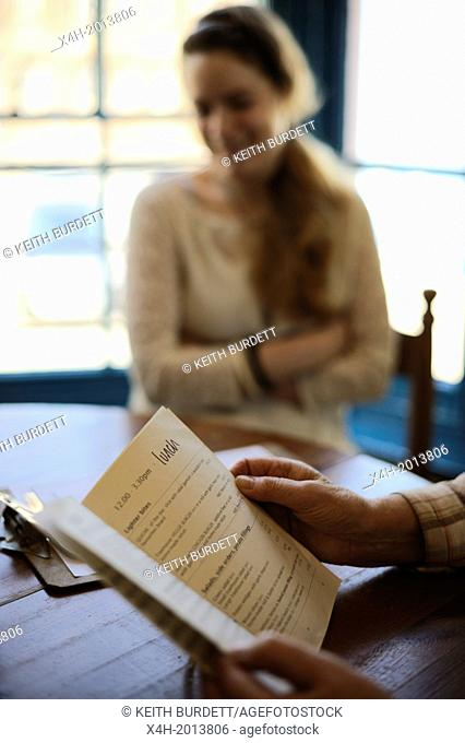 Young woman with her grandmother choosing from a menu at window seats in a restaurant at lunchtime, Wales, UK