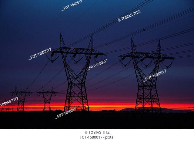 Silhouette electricity pylons on field against sky at dusk