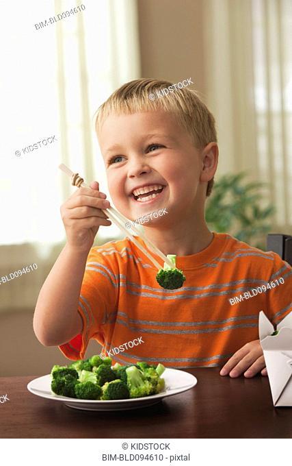 Smiling Caucasian boy eating broccoli