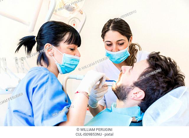 Dentist and dental nurse giving male patient dental examination