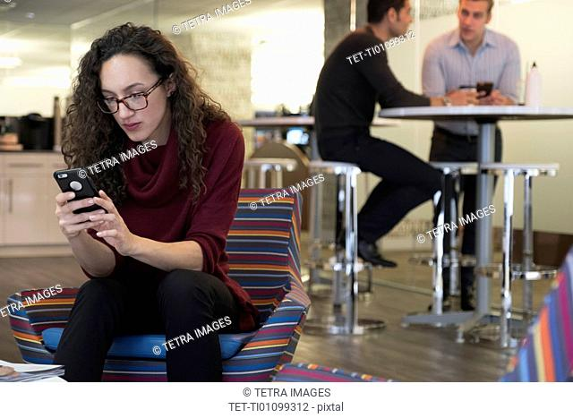 Young woman using mobile phone in common area