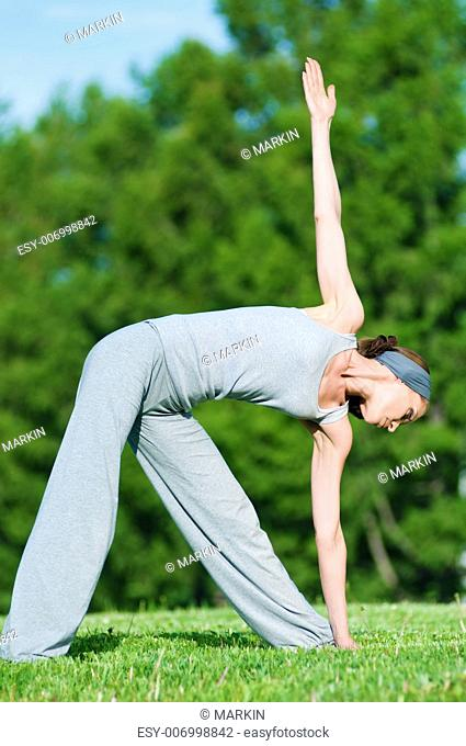 Beautiful woman doing stretching exercise on green grass at park. Yoga