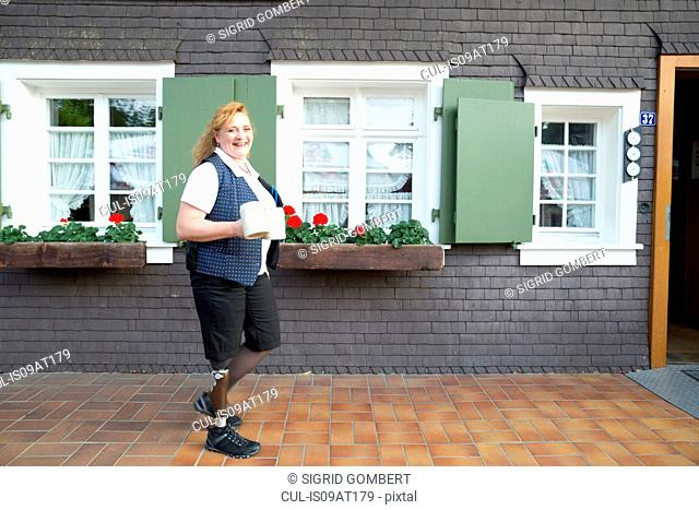 Mid adult woman with prosthetic leg, carrying mugs, outdoors