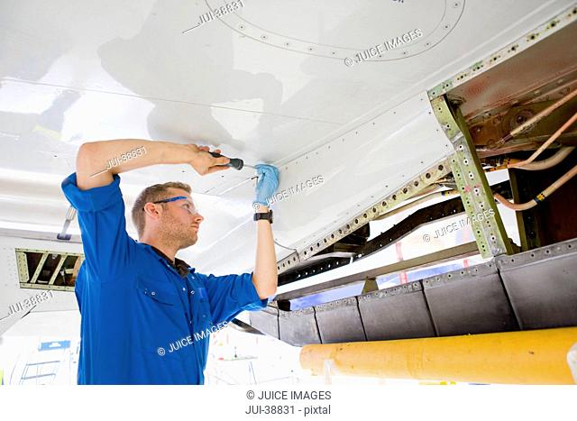 Engineer assembling wing of passenger jet in hangar