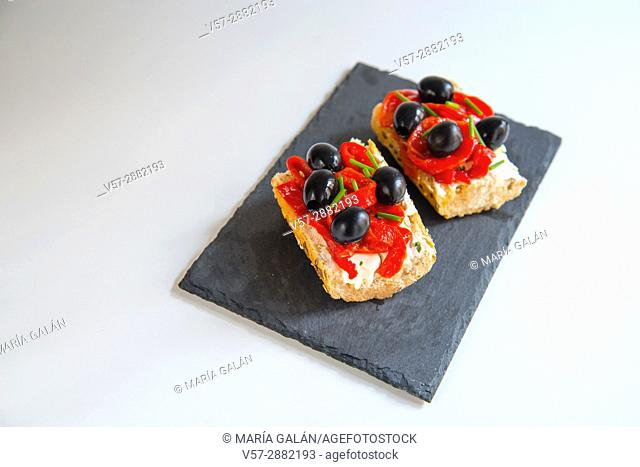 Spanish tapa: red peppers and black olives on toast with cheese cream and chives