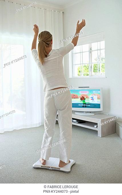Woman doing step aerobics and watching TV