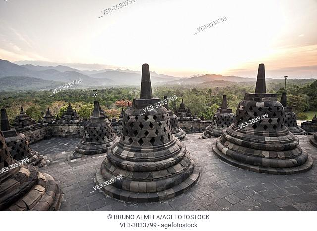 Sunset over unroofed pyramid of Borobudur Temple, crowned by bell-shaped stone domes (Magelang Regency, Central Java, Indonesia)