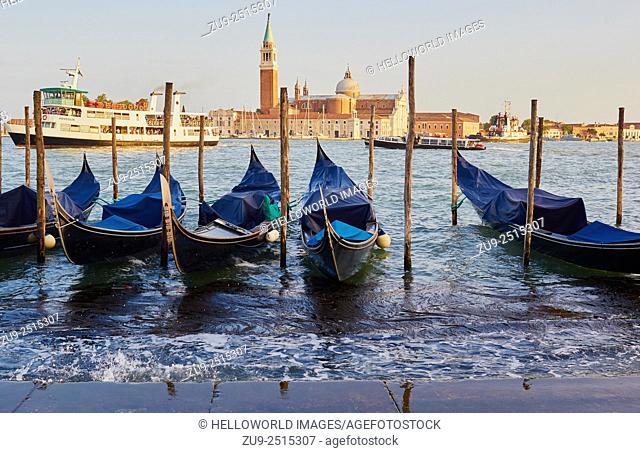 Gondolas moored on Venice waterfront with San Giorgio Maggiore island in background, Veneto, Italy, Europe