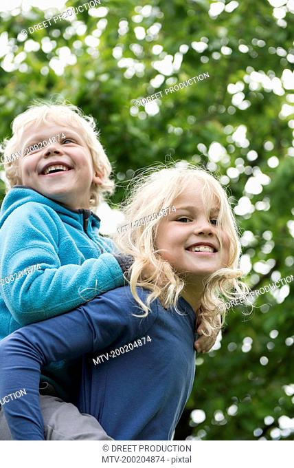 Young blonde girl carrying brother piggyback
