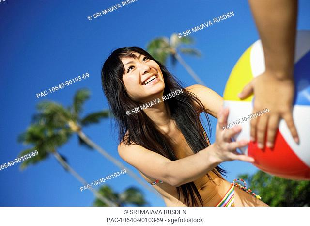 Young Japanese girl playing with beach ball