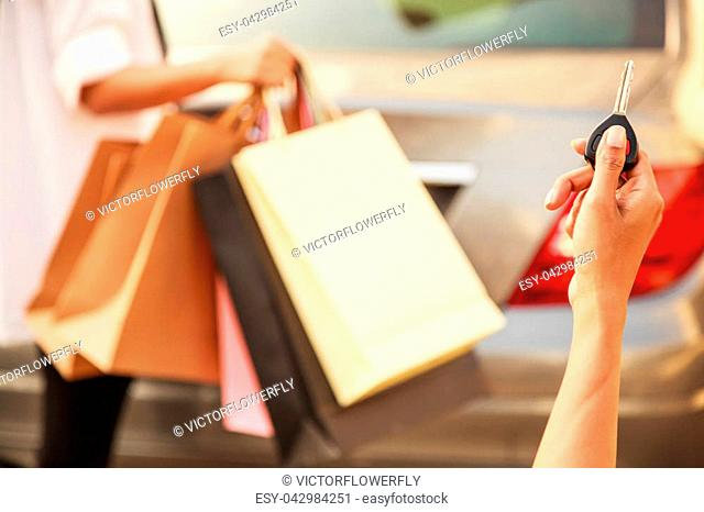 Female Ladies carrying Colorful Shopping Bags in the parking lots Concept. Lady hand using remote control to send signal to unlock car doors and trunk