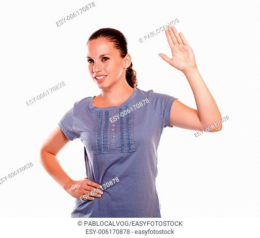 Portrait of a smiling young female greeting to the right on blue shirt standing over white background