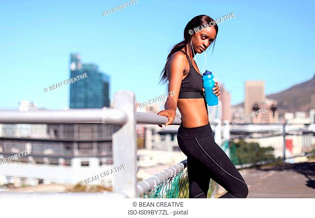 Young female runner listening to earphones leaning against city handrail, portrait, Cape Town, Western Cape, South Africa
