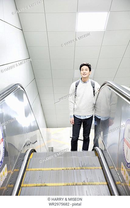 Young smiling man taking escalator up at subway station