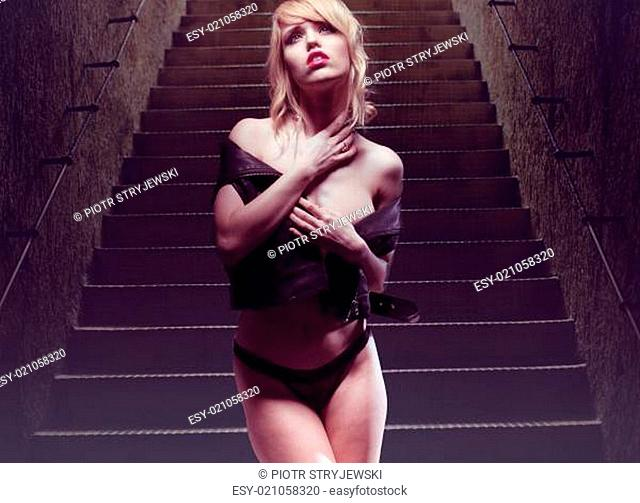 Portrait of a Sexy Young Blond Woman Posing in Black Leather Shirt and Underwear at the Stairs Provocatively While Looking Up