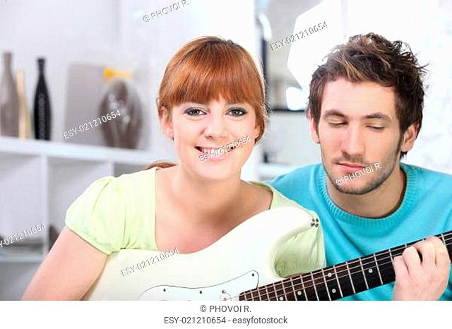 red-haired girl playing guitar in bedroom with boyfriend
