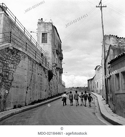 Some children walking hand in hand in the streets of the neighbourhood called Ragusa Ibla. Ragusa, 1955