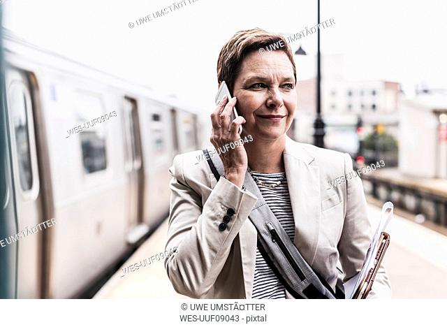 Mature woman using smart phone at commuter train station