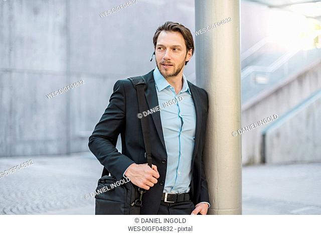 Businessman with laptop bag wearing headset outdoors