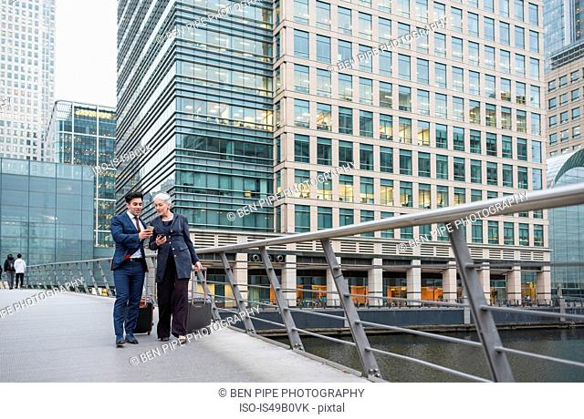 Businessman and businesswoman using mobile phone and pulling trolley luggage, Canary Wharf, London, UK