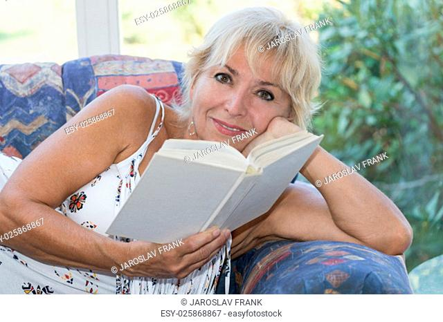 Attractive senior mature blond woman is lying on the couch and reading a book. She looking at the camera and she is hiding her cleavage by book