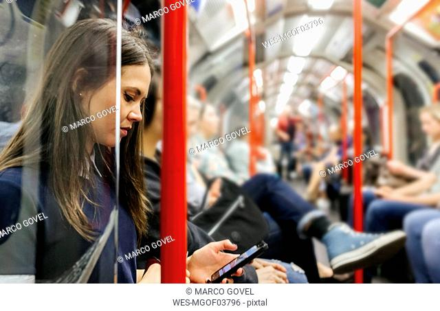UK, London, young woman in underground train looking at cell phone